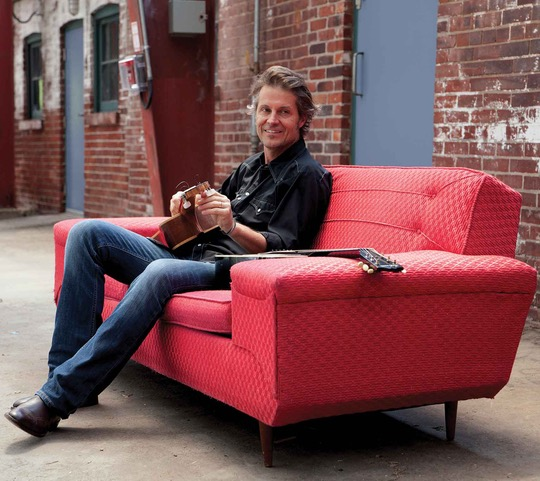 Jimmy cuddy sitting on a couch with guitar in hand